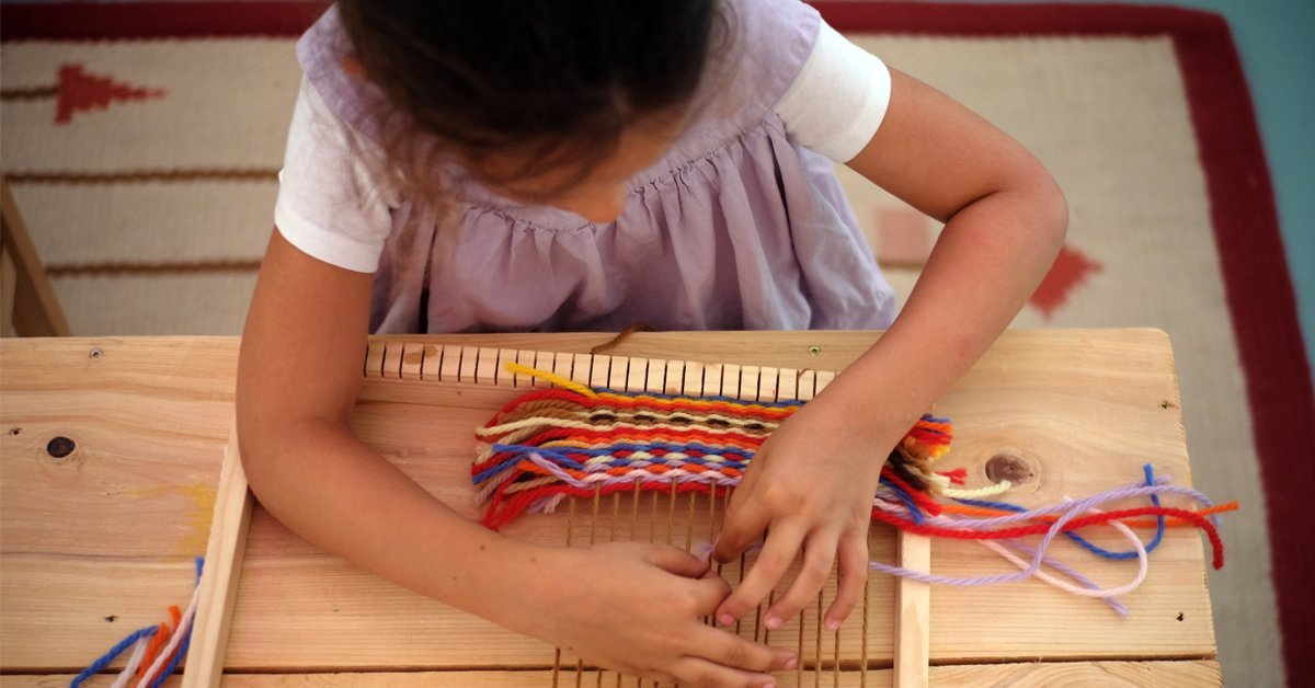 bambina lavora al telaio
